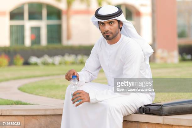 Portrait of Emirati businessman holding water bottle.,Portrait of Emirati businessman holding water bottle.