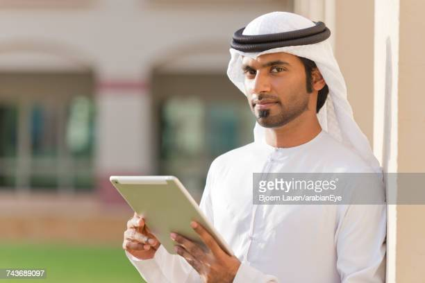 Portrait of Emirati businessman using digital tablet.