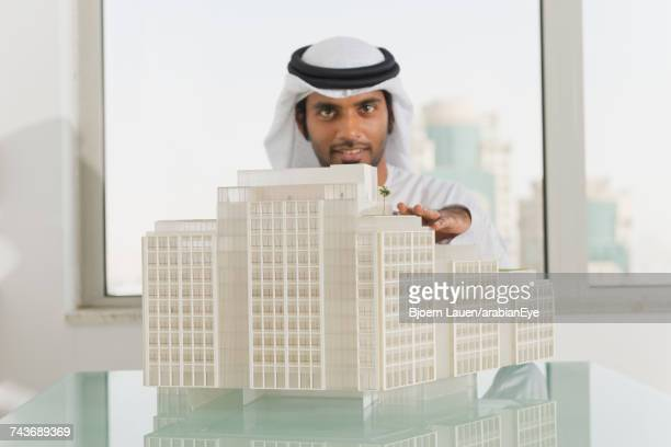 Portrait of Emirati businessman with architectural model at office.