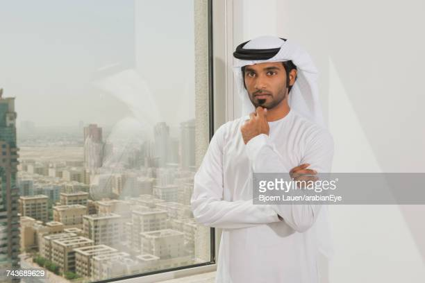 Portrait of Emirati businessman with hand on chin.