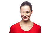 Portrait of funny positive winking woman in red t-shirt with freckles. looking at camera with toothy smile, studio shot. isolated on white background.
