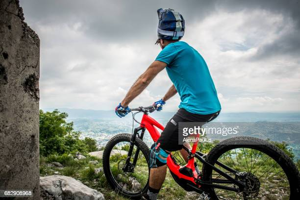Portrait of Enduro All Mountain E bike rider - adrenaline MTB trail - looking at view