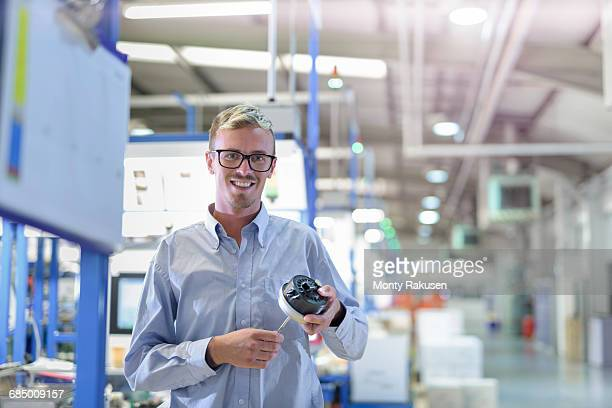 Portrait of engineer holding 3D printed exhaust valve actuator in factory