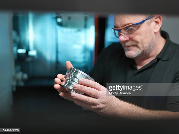 Portrait of engineer holding engineered part at CNC machine
