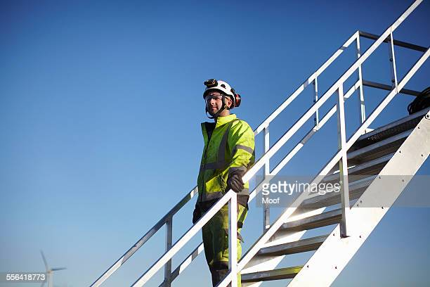 Portrait of engineer on steps, at wind farm