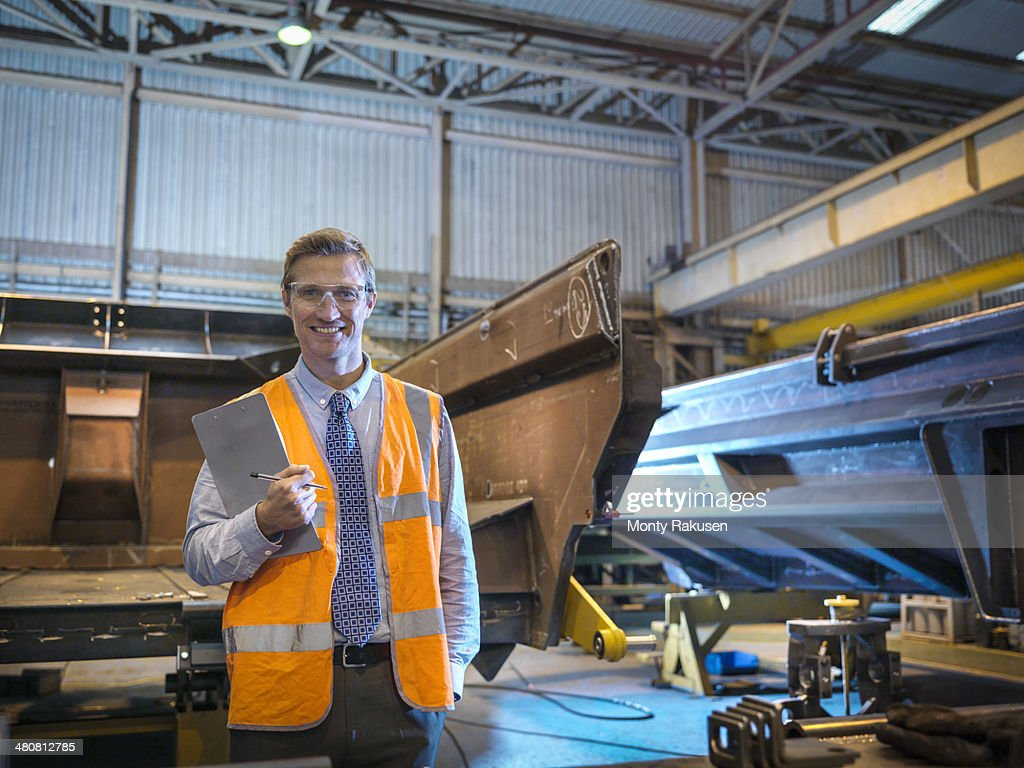 Portrait of engineer smiling in factory : Stock Photo