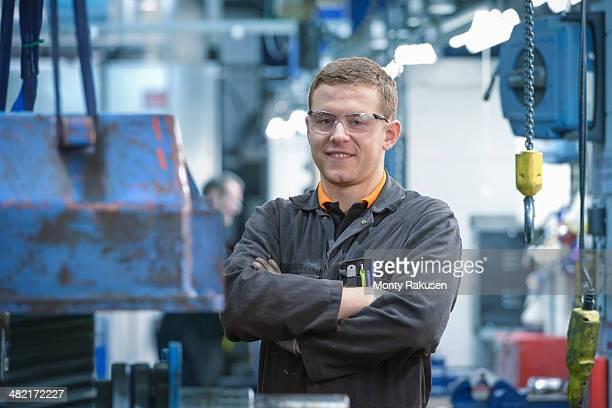 Portrait of engineering apprentice in engineering factory, smiling