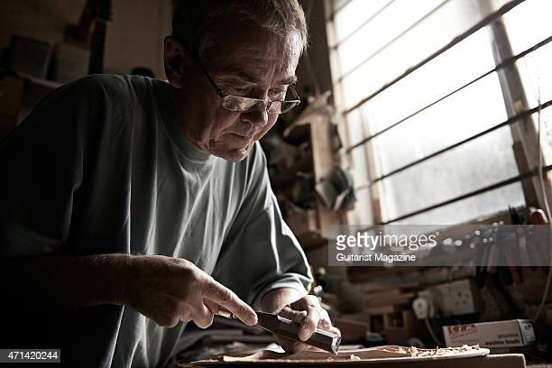 Portrait of English luthier Jonny Kinkead creating a handmade guitar at his workshop in Bristol on August 15 2014