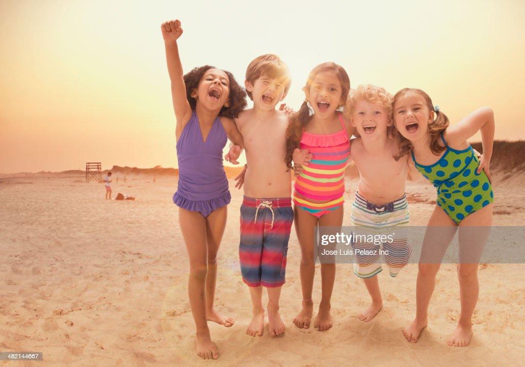 Portrait Of Enthusiastic Children Cheering On Beach Stock ...