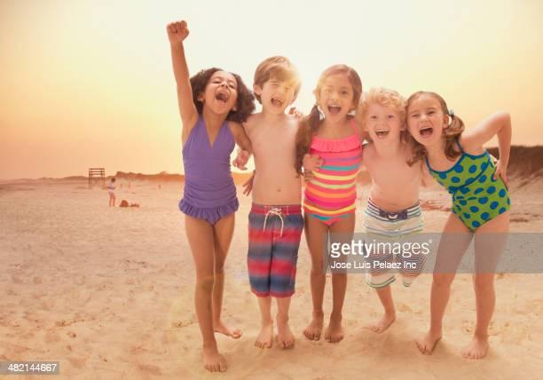 Portrait of enthusiastic children cheering on beach