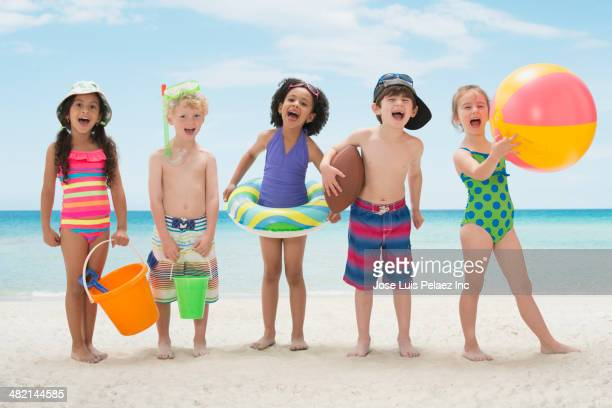 Portrait of enthusiastic children with toys on beach