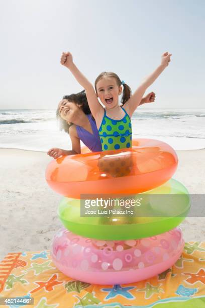 Portrait of enthusiastic girls playing in inflatable rings on beach