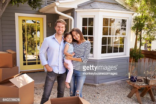 Portrait Of Excited Family Standing Outside New Home : Stock Photo