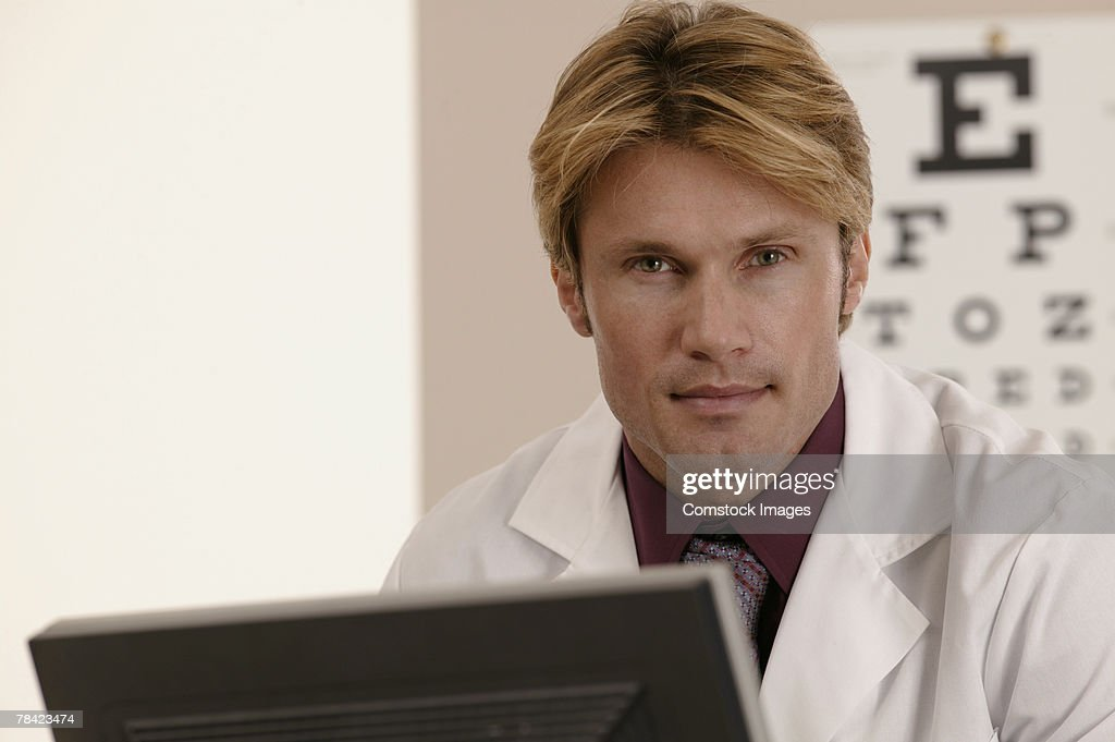 Portrait of eye doctor with eye chart behind him : Stock Photo