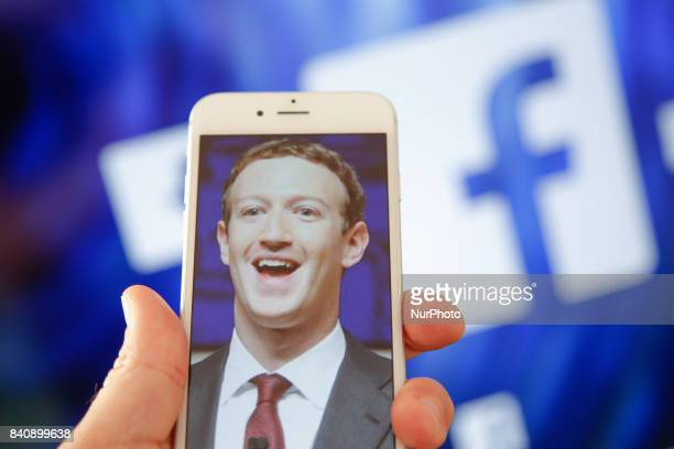 A portrait of Facebook found Mark Zuckerberg is seen on an iPhone in this photo illustration on 28 August 2017