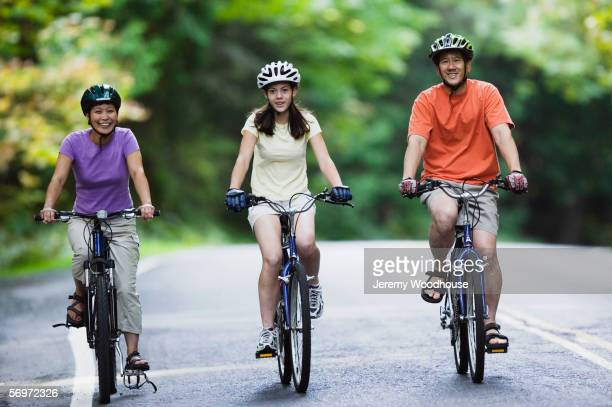 Portrait of family biking down road