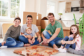 Portrait Of Family Celebrating Moving Into New Home With Pizza
