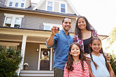 Portrait Of Family Holding Keys To New Home On Moving In Day