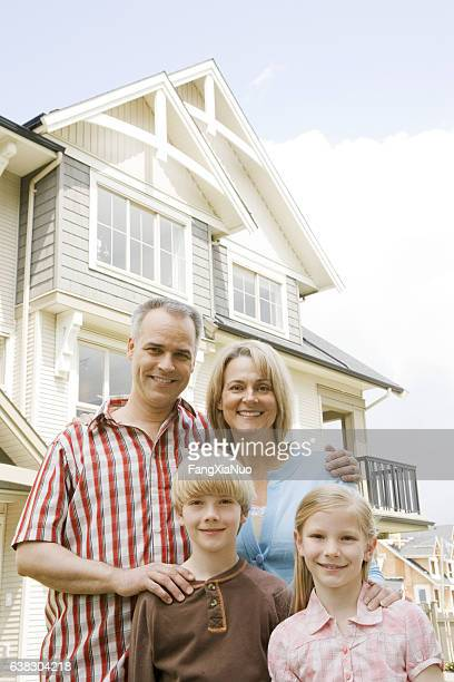 Portrait of family in front of suburban house