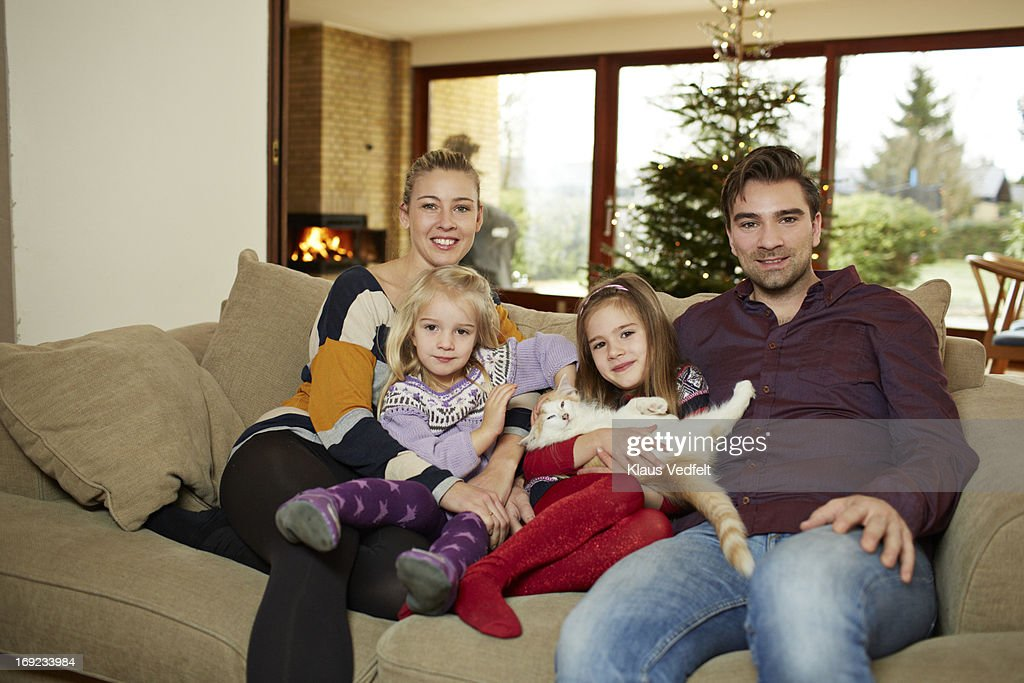 portrait of family of 4 in sofa with cat : Stock Photo