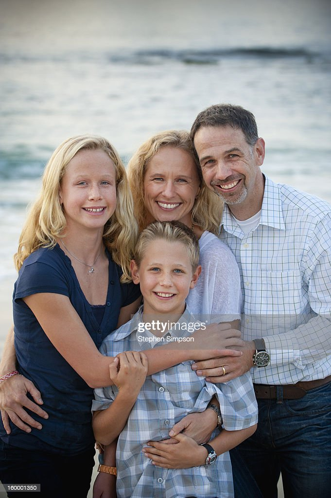 portrait of family of four at the beach : Stock Photo