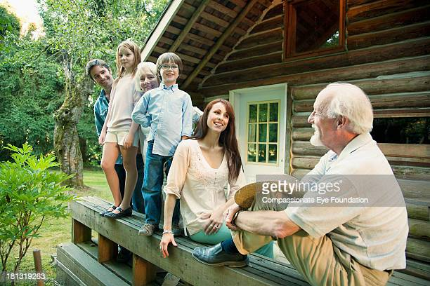 Portrait of family outside log cabin