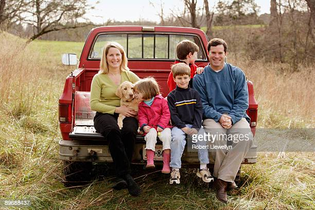 Portrait of family sitting on bed of pickup truck with dog