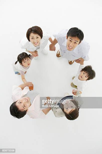 Portrait of family standing in circle, hand in hand, view from above, studio shot