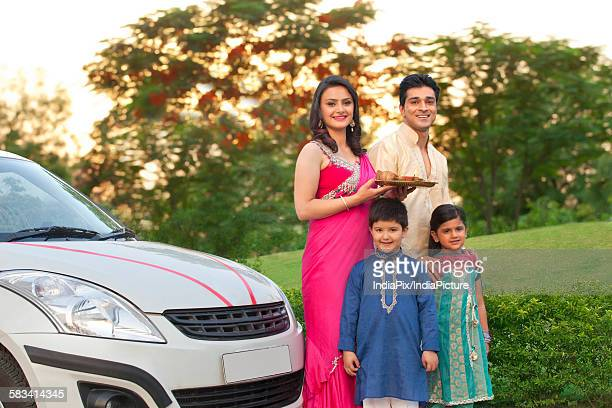 Portrait of family standing next to new car