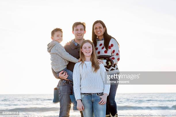 Portrait of family standing on seashore