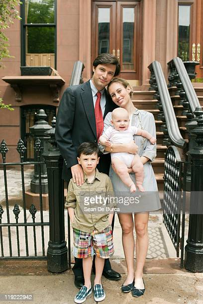 Portrait of family standing outside their home.