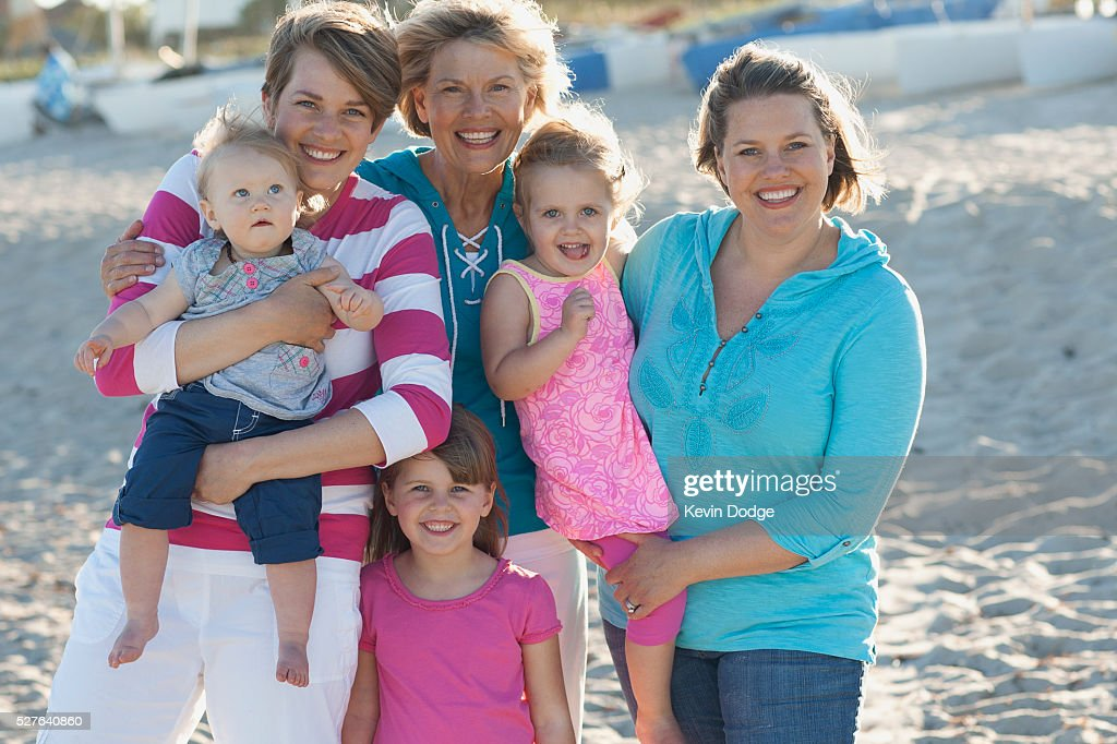 Portrait of family with children (12-23 months, 2-3, 4-5 years) on beach