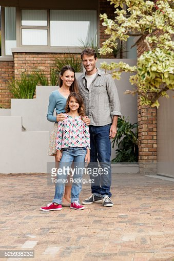 Portrait of family with teenage girl (13-15) standing next to house : Stock Photo