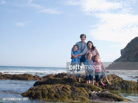 Portrait of family with three children (6-9) at seashore : Stock Photo