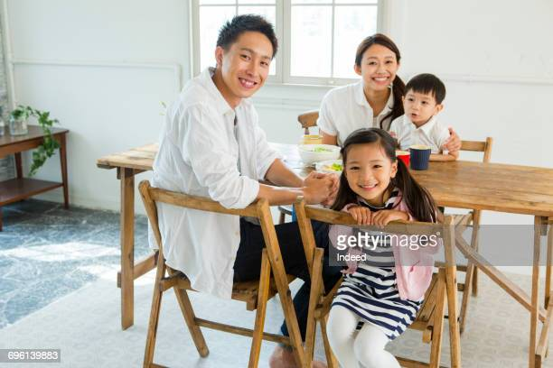 Portrait of family with two children at dining table