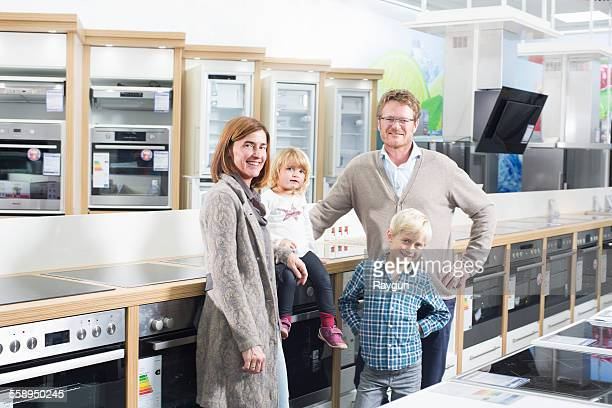 Portrait of family with two children browsing hobs in electronics store