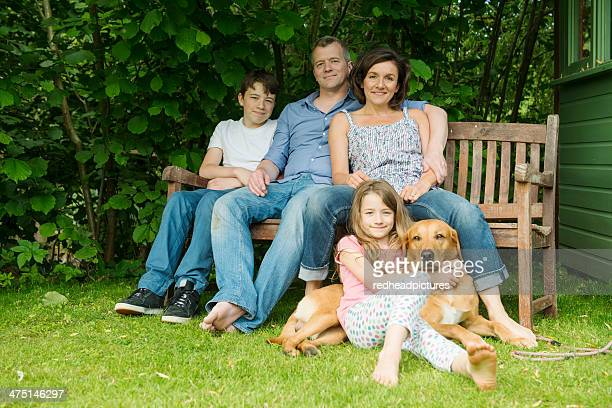 Portrait of family with two children sitting on garden bench with dog