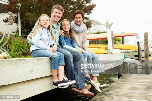 Portrait of family with two girls (6-7), (8-9) relaxing by water : ストックフォト