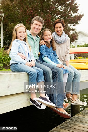 Portrait of family with two girls (6-7), (8-9) relaxing by water : Stockfoto