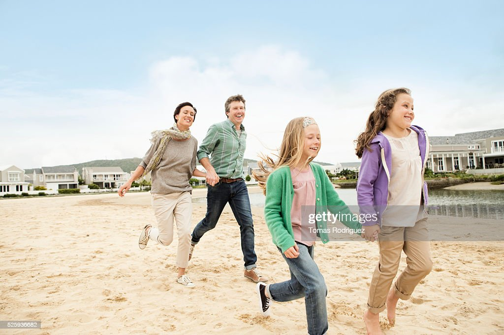 Portrait of family with two girls (6-7), (8-9) running along pond : Stock Photo