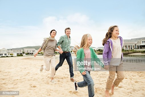 Portrait of family with two girls (6-7), (8-9) running along pond : Stock-Foto