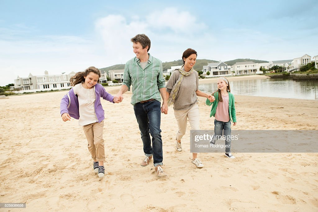 Portrait of family with two girls (6-7), (8-9) walking along pond : Foto de stock