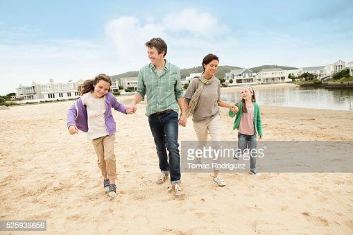 Portrait of family with two girls (6-7), (8-9) walking along pond : Stock Photo