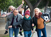 Cheerful active family with two smiling children spending weekend together outdoors