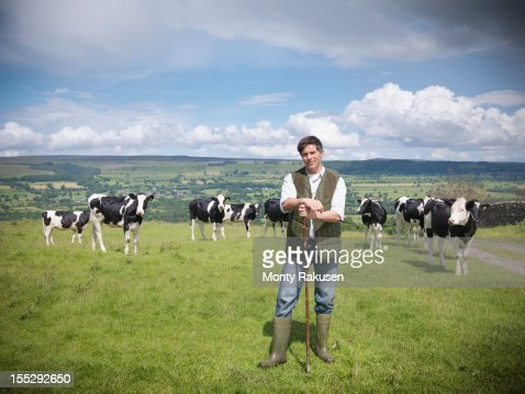 Portrait of farmer and cows in field