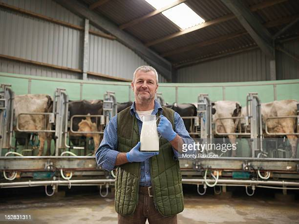 Portrait of farmer holding jug of milk in rotary milking parlour on dairy farm with cows