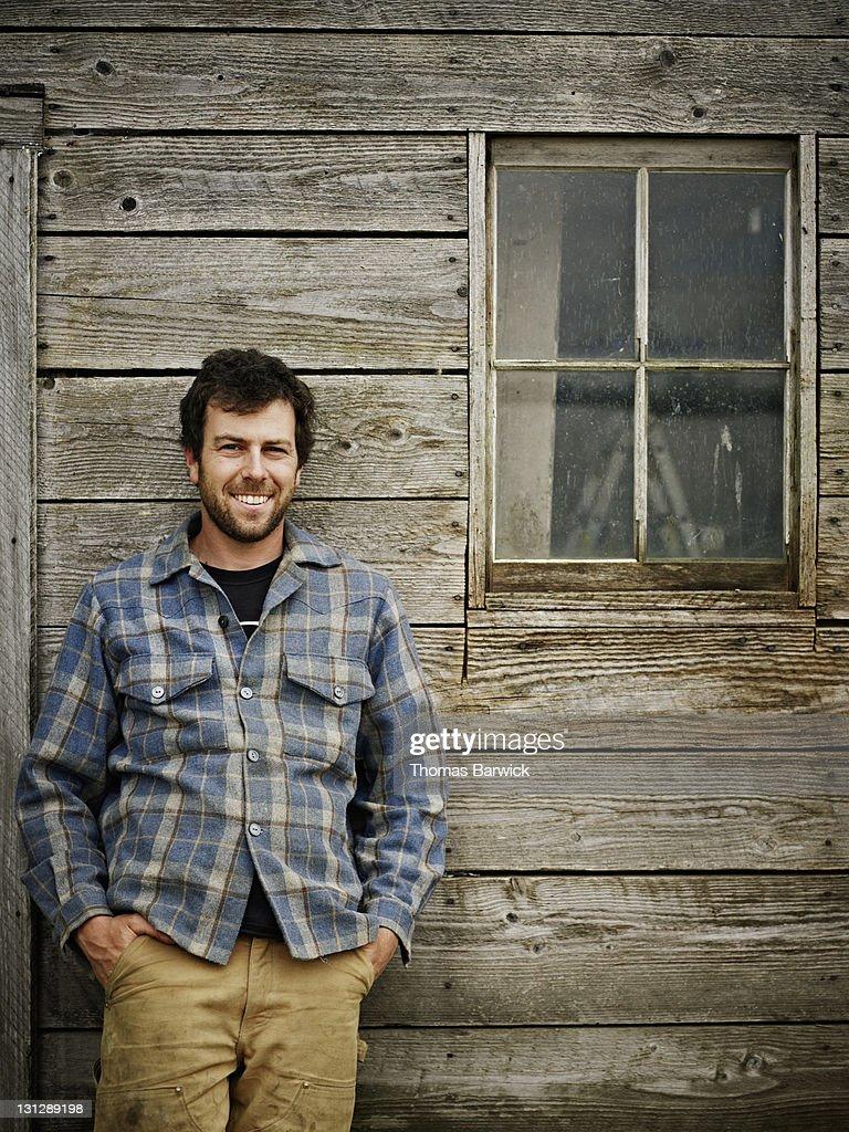 Portrait of farmer leaning against side of barn : Stock Photo