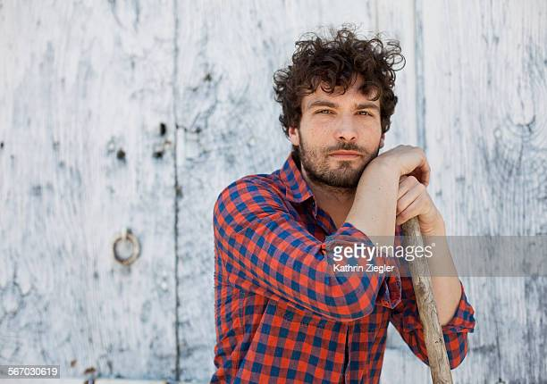 portrait of farmer leaning on gardening tool