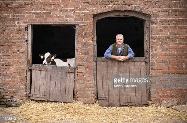 Portrait of farmer leaning on stable door with calf