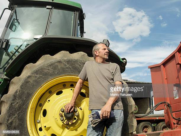 Portrait of farmer standing next to tractor, looking away
